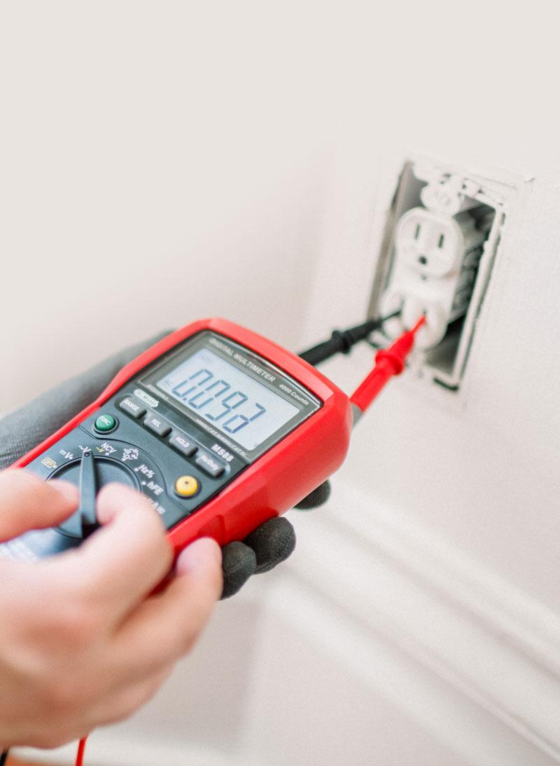électricien entrain de mesurer avec un multimètre une prise électrique